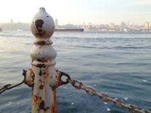 White rusting metal fence pole next to the sea in Istanbul stock photography