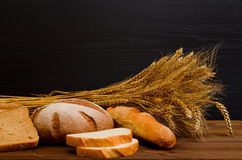 White and rye bread, a loaf, a sheaf on wooden table, black background. Space for text Stock Photography