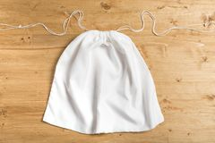 White sack bag on strings on wooden background, mock up.  royalty free stock images
