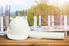 White safety hat and paper plan blueprint on wood table in working construction site housing building. With copy space add text Royalty Free Stock Images
