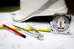 White safety helmet and drawing tools on naval architects working desk.  stock images