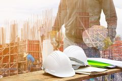 White safety helmet and paper plan blueprint on wood floor table with concept Double Exposure engineering in working building stock photography
