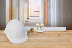 White safety helmet plastic, paper roll plan blueprint alarm clock time a rest at noon, bitcoin coin on wood floor table. And gypsum board wall interior stock image