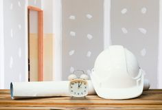 White safety helmet plastic, paper roll plan blueprint alarm clock time a rest at noon on wood floor table and gypsum board wall. Remodel interior with copy stock images