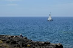 White sail boat in blue sea. And fisherman sitting on the rock in Tenerife Canary islands Royalty Free Stock Photography