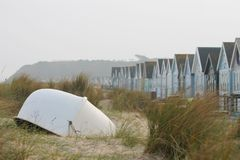 Boat with beach huts at Mudeford, Dorset, UK stock photography