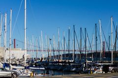 White sail boats in a bay in Lisbon with the 25th April bridge royalty free stock photos