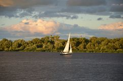 White sail and dramatic apocaliptic sky, Dnepr river. White sail and dramatic apocaliptic sky in summer, Dnepr river, sky with different colourings, Kiev stock photos