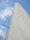 White sail under blue sky stock photography