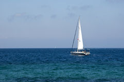 White sail on a yacht in the blue sea Stock Photography