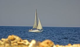 White sailboat in the blue sea. Yacht against the blue sea stock photo