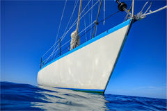 Sailboat in calm blue water with reflections. White Sailboat in calm surface of blue ocean water with reflections and clear sky on backgound stock image