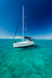 White sailboat floats on clear turquoise blue Caribbean waters Royalty Free Stock Photo