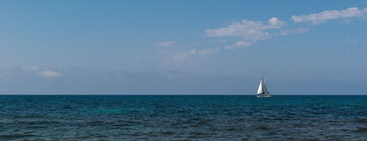 White sailboat on the horizon Royalty Free Stock Images