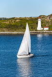 White Sailboat and Lighthouse with Blue water Royalty Free Stock Photos
