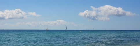 White sailboat in the Mediterranean sea, beautiful cumulus clouds Royalty Free Stock Image