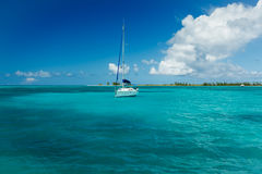 White sailboat moored in bright turquoise blue Caribbean waters Royalty Free Stock Images