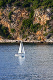 White Sailboat Past Golden Cliffs Royalty Free Stock Images