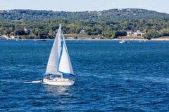 White Sailboat Past Maine Coast. Sailboat off the beautiful coast of Rockland, Maine Stock Photos