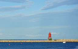 White Sailboat and Red Lighthouse in Harbor Royalty Free Stock Photos
