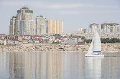 White sailboat. Sails along the beautiful city of Aktau (Kazakhstan Stock Photos