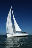 White sailboat taking speed under blue sky Royalty Free Stock Photo