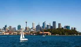 Sailboat crossing the deep blue waters of Sydney Harbor against a backdrop of the city skyline Royalty Free Stock Photography