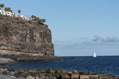 White sailboat under a cliff. In island Stock Photo
