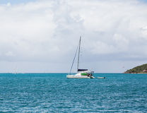 White Sailboat Under Mast on Blue Water Stock Photo