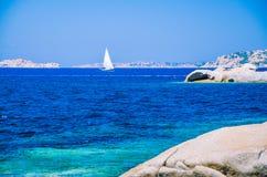 White sailboat, yacht between granite rocks in sea, amazing azure water, Sardinia, Italy Royalty Free Stock Photos