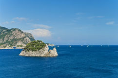 White sailboats in sea floating among rocky islands Stock Photos