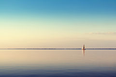 White sailing boat on calm waters. Water landscape with white sailing boat on calm waters in the light of the sunset. Toned and processing photos Royalty Free Stock Photo
