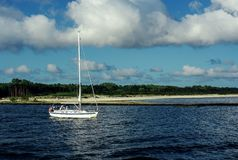 White sailing boat under way using engine moving outbound. Background is beach. stock photography