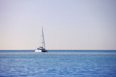 White sailing catamaran on calm sea Stock Photography