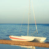 White sailing yacht in the beach on calm sea. Square, toned Royalty Free Stock Photo