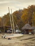 White sailing yacht on the shore set for storage in the winter time. Preservation of the yacht with a sail on the shore Stock Photos