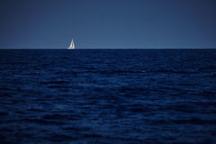 The white sails of yachts on the background of sea and sky Stock Images