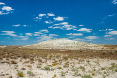 White salt hill in the desert and man. The rich scenery. Desert with salt white sand, small dry bushes. Far white hill, and on it stands a man. Very bright blue royalty free stock photography