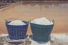 White salt in plastic basket for water evaporation place on edge of salt lake at countryside of Thailand. Close up white salt in plastic basket for water stock image