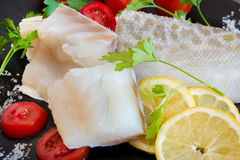 White salted codfish. Pieces of white raw salted  codfish with tomatoes and parsley on slate plate Stock Image