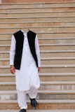White Salwar Kameez with Black Waistcoat and Black Peshawari Shoes without the head. White Salwar Kameez with Black Waistcoat and Black Peshawari Shoes and Stock Photography