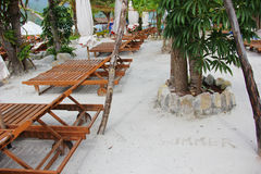The white sand beach and the inscription summer. White fine sand on the beach, and the inscription summer, wooden deck chairs, various green plants, furled Royalty Free Stock Images