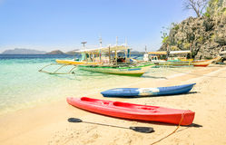 White sand beach with longtail boats and kayaks in Coron Palawan Stock Images