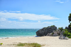 White sand beach with rocks and turquoise sea water on a bright Stock Image