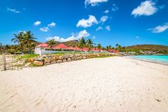 St Jean beach, St Barts, Caribbean. White sand beach, Saint Jean Beach, blue sky with some white clouds. Buildings and palm trees along the coastline of St Barts stock photo
