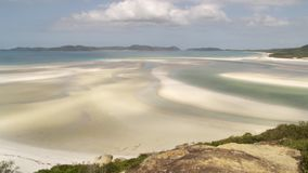 White sand beach at sight. A pan to left shot of a white sand turquoise water beach. Green trees are seen in the shot stock footage