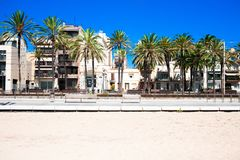 White sand beach with train station in Badalona, Costa Brava, Sp. Ain. Palms trees, hotel buildings, apartments and blue sky at summer day Royalty Free Stock Images
