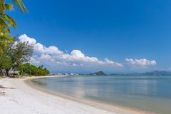 White sand beach , turquoise water and green lush trees on the foreground in south of Thailand.  stock photos