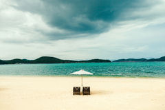 White sand beach with two sunbeds, umbrella, without people. Luxury beach resort with white sand beach with two sunbeds, umbrella, without people and stormy sky royalty free stock image
