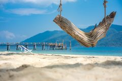 White sand beach wooden swing tranquil relax beautiful sea. Tropical beach for summer and vacation Stock Photo